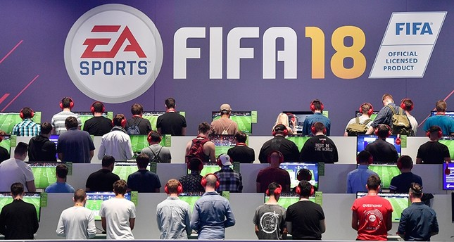 Visitors play the latest FIFA 18 soccer game from EA Sports at the Gamescom fair for computer games in Cologne, Germany, Aug. 22, 2017. (AP Photo)