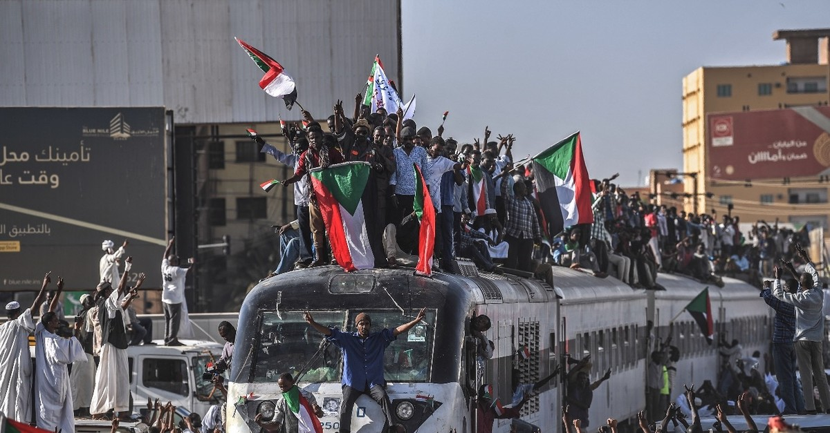 Sudanese protesters from the city of Atbara, sitting atop a train, cheer upon arriving at the Bahari station in Khartoum, April 22, 2019.