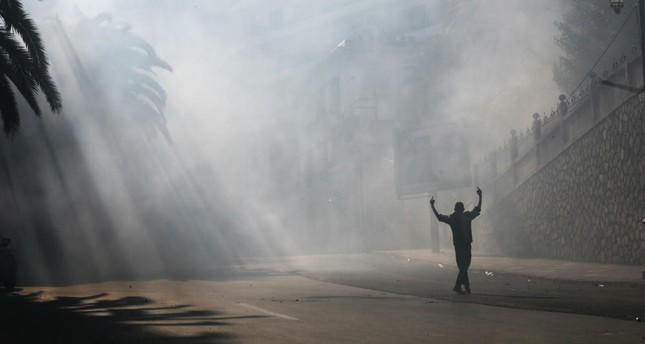 A protester gestures during clashes with police officers at a demonstration against the country's leadership, in Algiers, Friday, April 12, 2019.