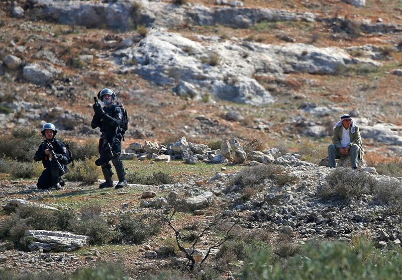 Israeli security forces fire tear gas toward Palestinian protesters during a demonstration against Israeli land seizures for Jewish settlements, in the village of Ras Karkar, near Ramallah in the occupied West Bank on Nov. 9, 2018. (AFP Photo)