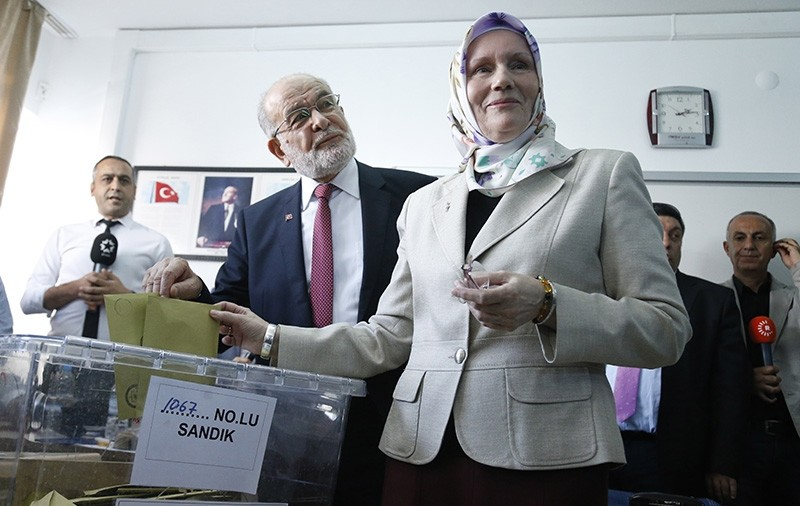 Temel Karamollaou011flu (C), the leader of Saadet Party, and his wife Ayu015fe Yasemin (R) cast their vote for the Turkish presidential and parliamentary elections in Ankara, Turkey, June 24, 2018. (EPA Photo)