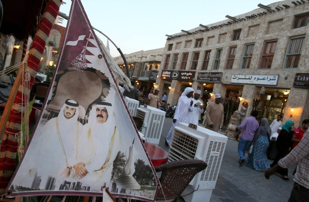Taken in 2014, the photo shows people walking past a banner bearing portraits of former Emir of Qatar Sheikh Hamad bin Halifa al Thani (R) and his son current leader SheikhTamim bin Hamad al Thani displayed at Souq Waqf in Qatar capital Doha.