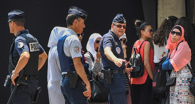 French police officers arrest a group of women on May 26, 2017 outside the luxury Martinez hotel in Cannes, southern France, before their attempt to take part in a bathing in burkini swimsuit on a beach of Cannes. (AFP Photo)