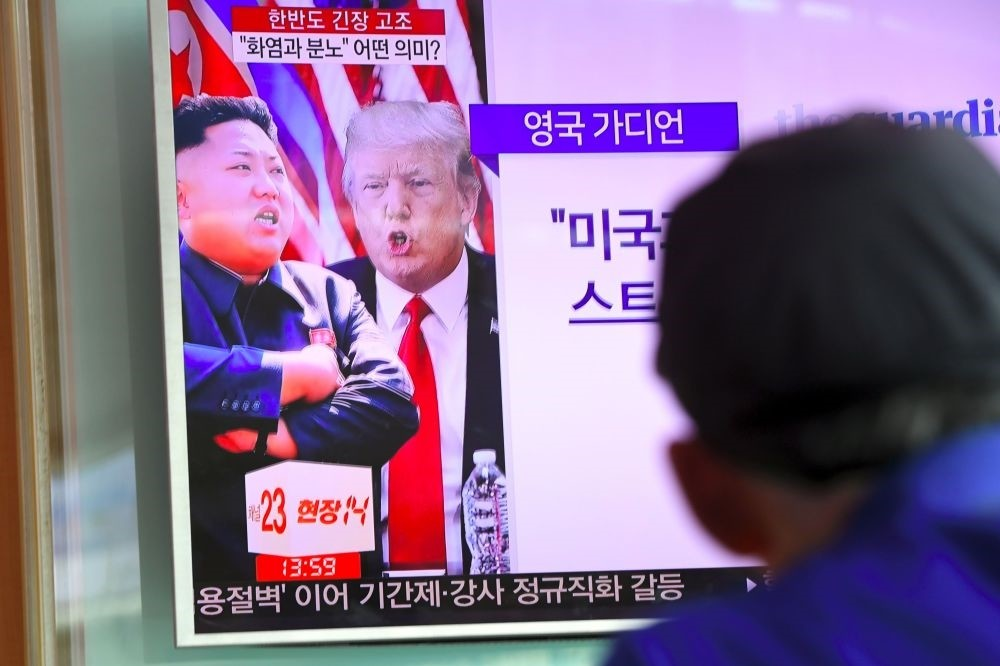 A man watches a television news program showing North Korean leader Kim Jong Un and U.S. President Donald Trump at a railway station in Seoul, Aug. 9, 2017.