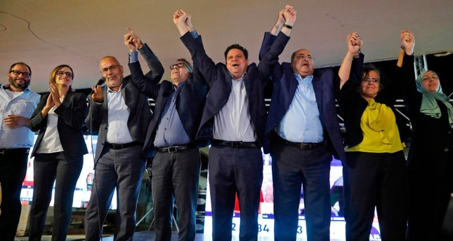 Joint List candidates celebrate before supporters at the alliance's campaign headquarters in the northern Israeli city of Nazareth on September 17, 2019, as the first exit polls are announced on television. AFP Photo