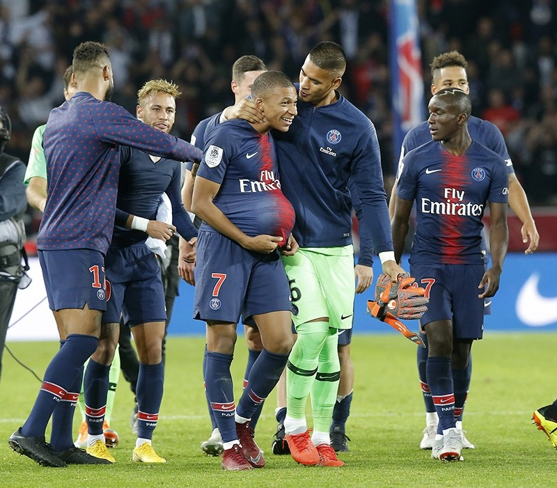 PSG's goalkeeper Alphonse Areola congratulates PSG's Kylian Mbappe after the French League One soccer match between Paris-Saint-Germain and Lyon at the Parc des Princes stadium in Paris, France, Sunday, Oct. 7, 2018. (AP Photo)