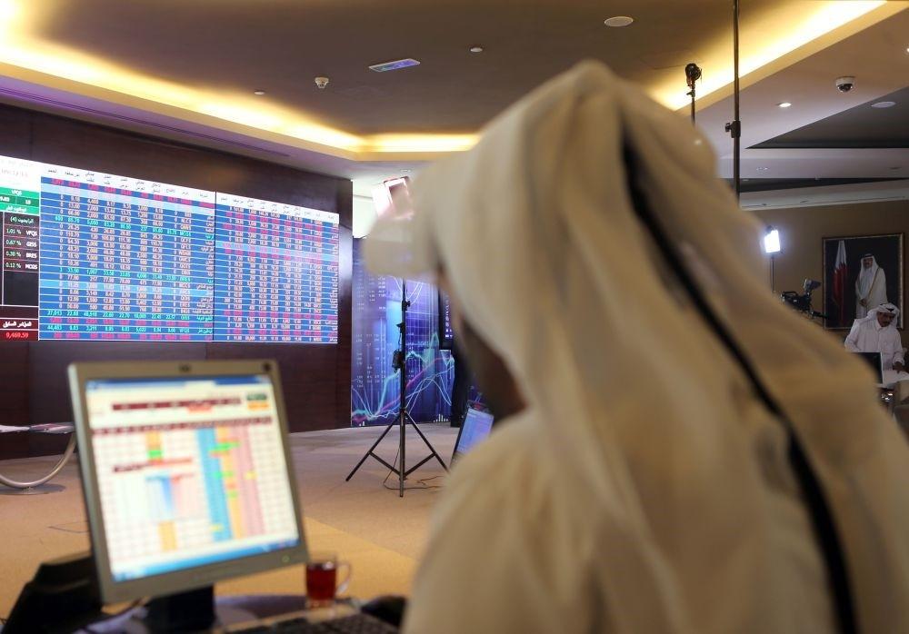 A Qatari trader follows the stock market at the Qatari stock exchange in Doha.