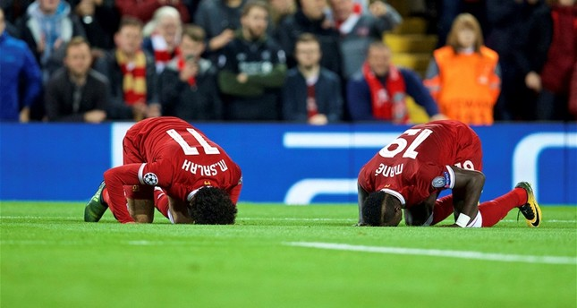 Liverpool's Mohamed Salah, left, and his teammate Sadio Mane performing sujood, or prostrating in Muslim prayer, during the UEFA Champions League Group E match between Liverpool and Sevilla at Anfield.Liverpool, U.K.