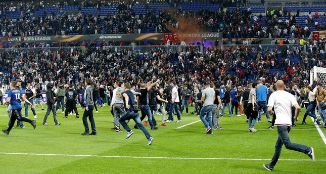 Supporters invade the pitch before the UEFA Europa League quarter final, first leg soccer match between Olympique Lyon and Beu015fiktau015f Istanbul. (EPA Photo)