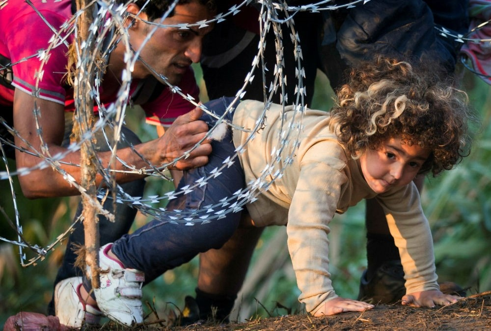 A refugee girl passes under razor wire as she crosses from Serbia to Hungary, in Roszke.