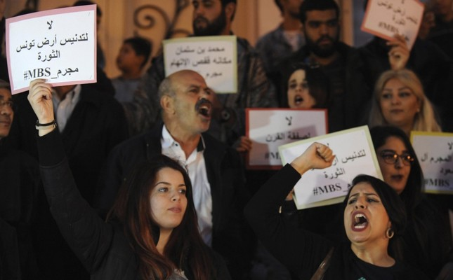"Protestors hold placards reading in Arabic ""no to the desecration of Tunisia, the land of the revolution"" during a protest against the visit of MBS in Tunis, Tunisia, Nov. 26."