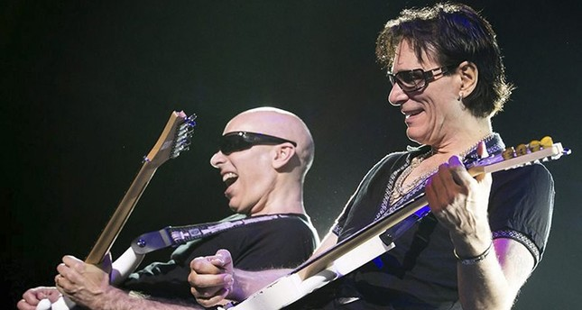 US guitarists Joe Satriani (L) and Steve Vai (R) perform during their G3 tour concert at the Papp Laszlo Budapest Sportsarena in Budapest, Hungary, 01 August 2012. (EPA)