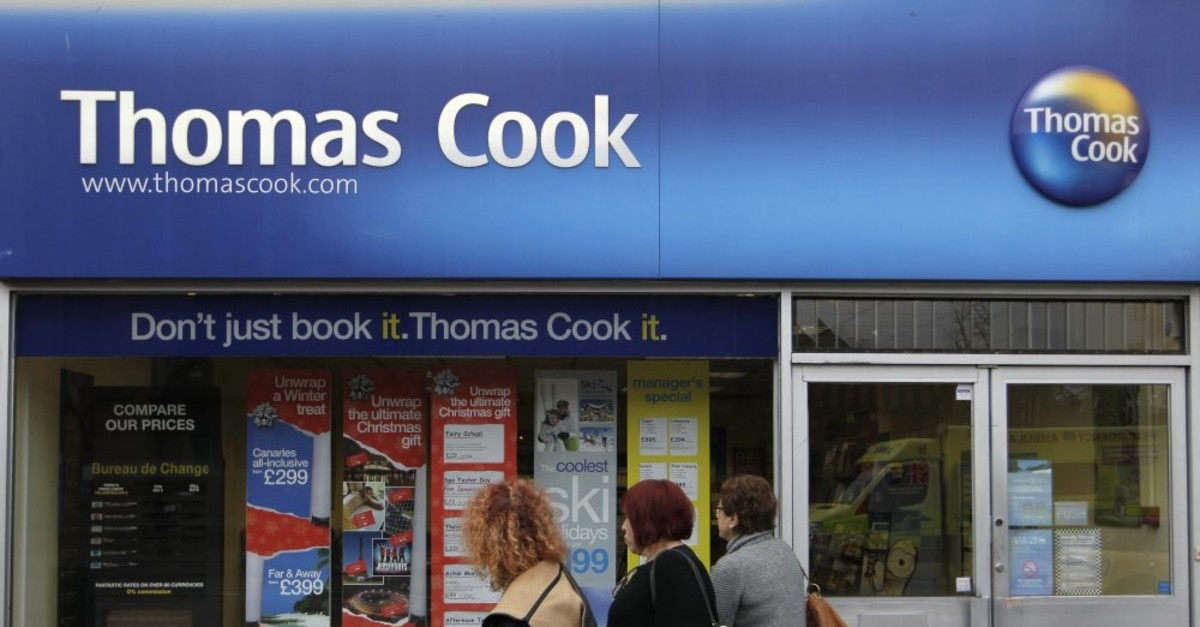People walk-by a branch of Thomas Cook travel agent in Borehamwood, north London, Nov. 22, 2011.