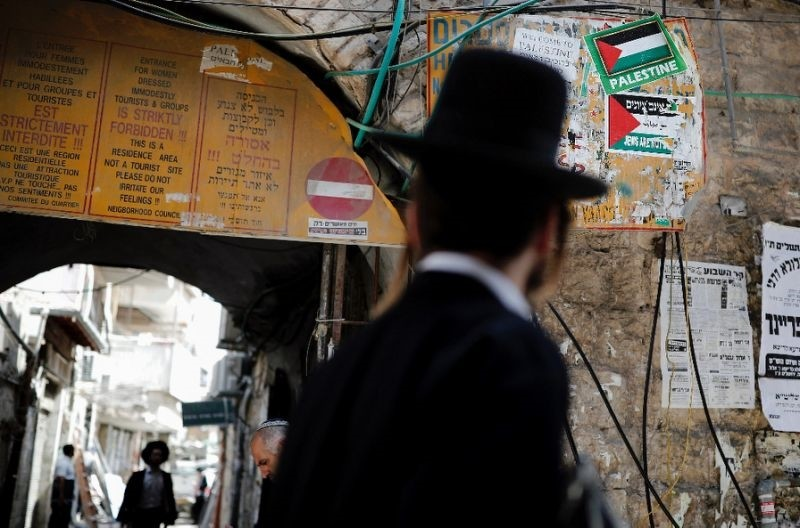 An Ultra-Orthodox Jewish man walks past signs forbidding ,immodestly dressed, women from entering part of Jerusalem's ultra-Orthodox neighborhood of Mea Shearim on September 13, 2017 (AFP Photo)