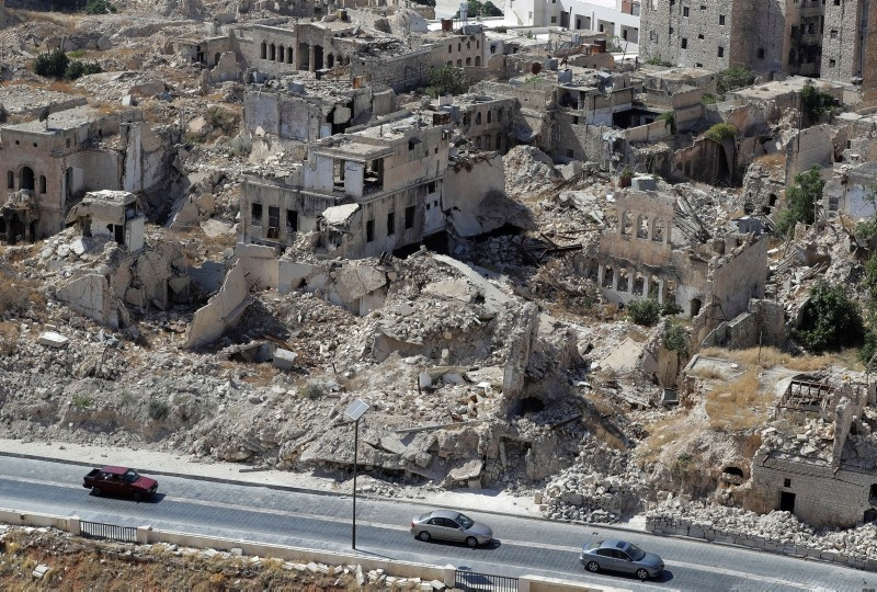 In this photo taken on Thursday, Aug. 16, 2018, people drive their cars past destroyed buildings in the city of Aleppo, Syria. (AP Photo)
