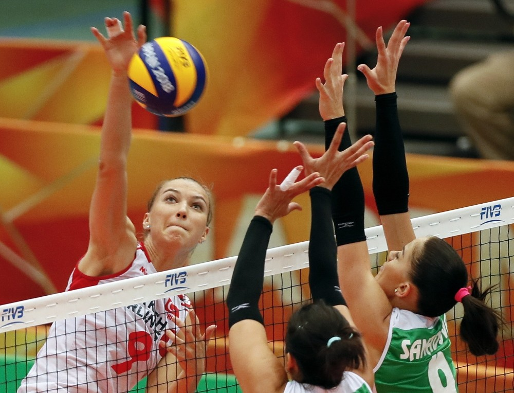 Melissa u0130smailou011flu (L) spikes the ball over blocks by Azerbaijan during the FIVB Women's World Championship second round Pool F match in Osaka, Oct. 10.