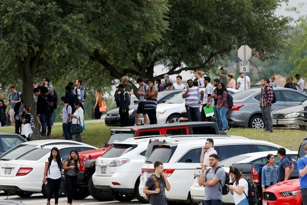 People stand in the parking lot while Irving police officers work at the shooting scene on the North Lake College campus in Irving, Texas, Wednesday, May 3, 2017.  (AP Photo)