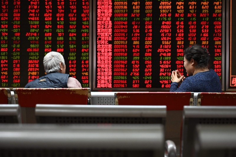 Two women sit in front of screens showing stock prices at a securities company in Beijing on January 21, 2019. (AFP Photo)