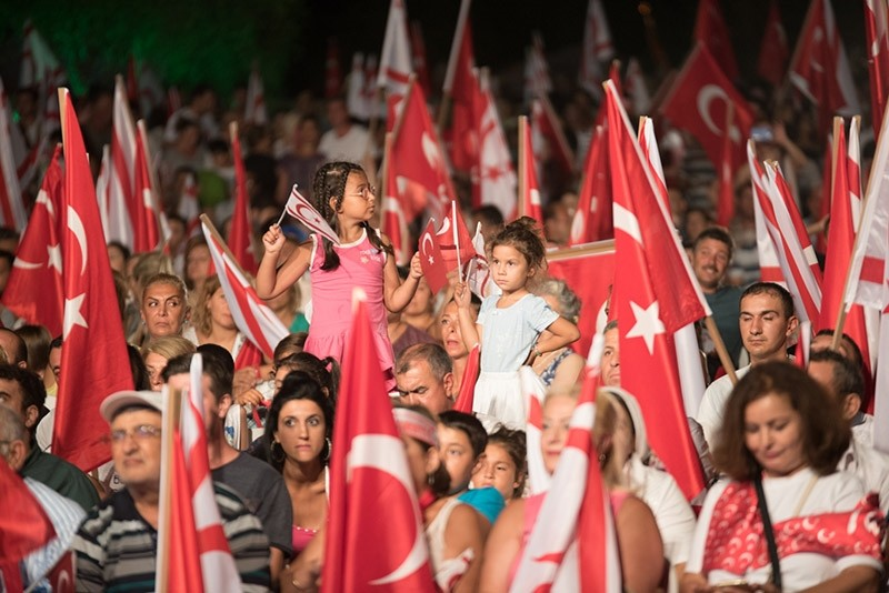 People gather with Turkish and TRNC flags to celebrate Peace and Freedom Day at Yavuz u00c7u0131karma (Five Mile) Beach, which was used by Turkish Army to launch their operation in 1974, Turkish Republic of Northern Cyprus, July 20, 2017. (AA Photo)