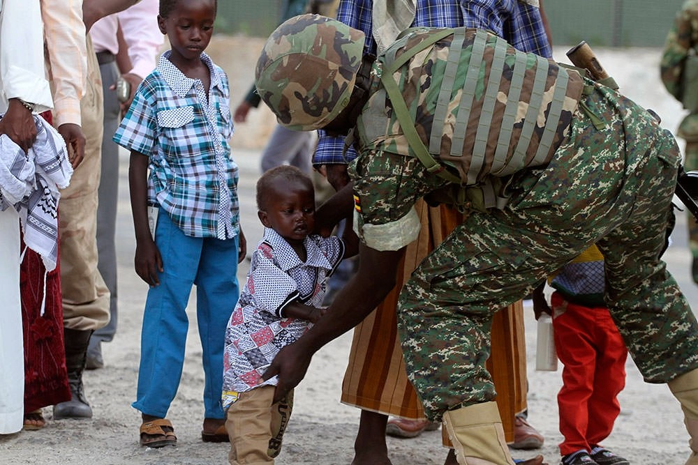 A soldier serving in the African Union Mission in Somalia frisks a Muslim child before allowing entry to attend Eid al-Fitr prayers