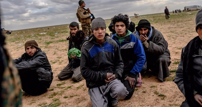 Men and boys suspected of being Daesh members wait to be searched by YPG militants after leaving the Daesh's last holdout of Baghouz, in Syria's northern Deir el-Zour province on Feb. 27, 2019.