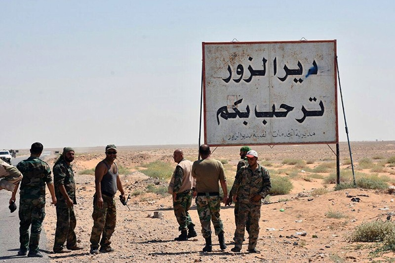 This photo released Sept. 3, 2017 by the Syrian official news agency SANA, shows Syrian troops and pro-regime gunmen standing next to a placard in Arabic which reads, ,Deir el-Zour welcomes you,, Deir el-Zour, Syria. (SANA via AP)
