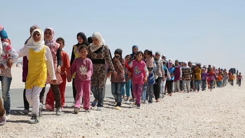 Syrian refugees march in a refugee camp in Jordan. (FILE Photo)