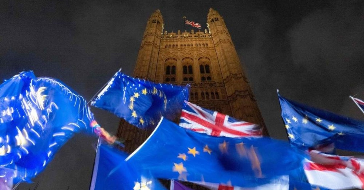 EU and UK flags flutter in the breeze as pro- and anti-Brexit demonstrators protest outside of the Houses of Parliament in central London, Oct. 21, 2019. (AFP Photo)