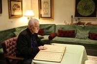 الفنان التركي منير إربورو يقرأ في نسخة القرآن الكريم المحفورة على الخشب (الأناضول)