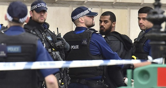Police officers talk to a man at the scene after a person was arrested following an incident in Whitehall in London, Thursday April 27, 2017. (AP Photo)