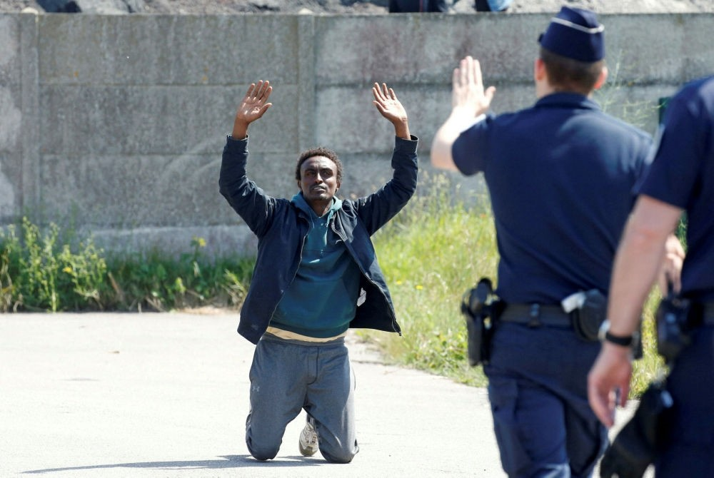 French riot police signal to a migrant on his knees as French authorities block their access to a food distribution point in Calais, France, June 1.