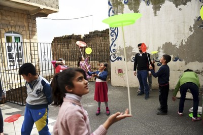 Syrian children perfom during a circus class on the roof top of a building.