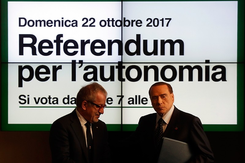Former Italian Premier and Forza Italia (Go Italy) Leader Silvio Berlusconi, right, and Lombardy Region President Roberto Maroni stand in front of a poster reading: Sunday, Oct. 22, 2017 (AP Photo)