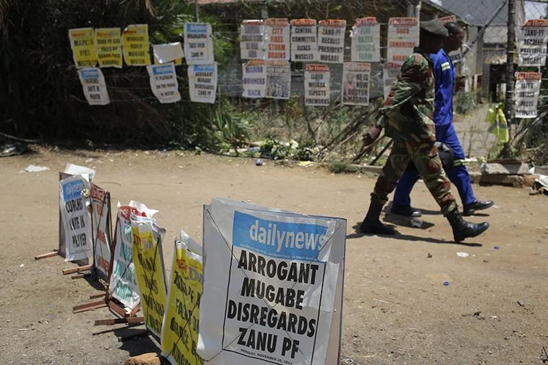 A soldier walks past news paper headlines referring to President Robert Mugabe, Harare, Zimbabwe, Nov. 20, 2017. (EPA Photo)