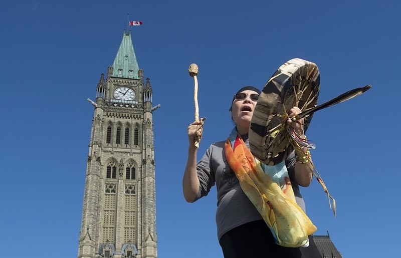 In this Oct. 6, 2017 file photo, Marcia Brown Martel plays her drum and sings outside Parliament following a government news conference announcing a compensation package for indigenous victims of the ,Sixties Scoop, (AP Photo)
