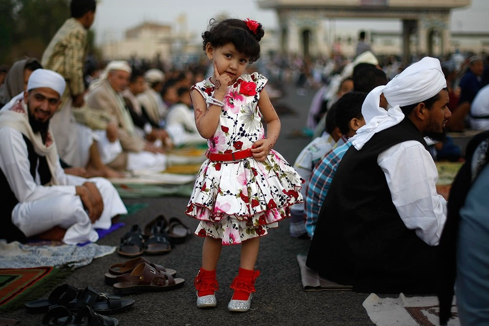 A Yemeni girl poses for a photograph as she attends the Eid al-Fitr prayer with her father