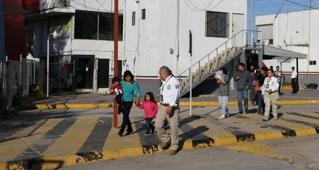 Asylum seekers are escorted by Mexican immigration officials as they are sent back to Mexico from the U.S. under the Remain in Mexico program officially named Migrant Protection Protocols, in Matamoros, Tamaulipas, Mexico, Oct. 28, 2019. (Reuters)