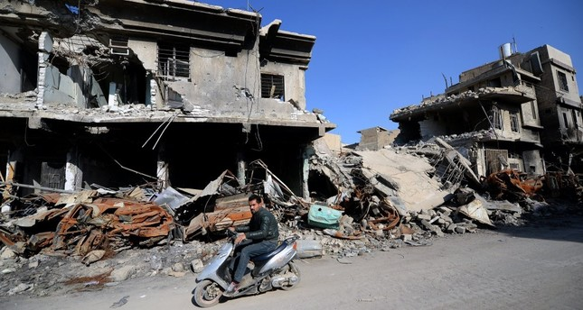 A man rides a scooter near destroyed buildings at the old city area in western Mosul months after the province of Nineveh was recaptured from Daesh militants.