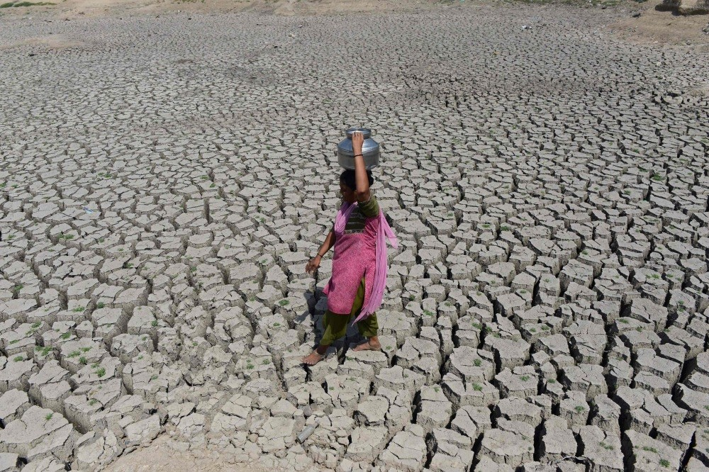 An Indian woman walks on the parched bed of Chandola Lake with a metal pot on her head to fetch water in Ahmedabad. 2016 was marked by 797 extreme climate-related events, the report published in The Lancet medical journal said.