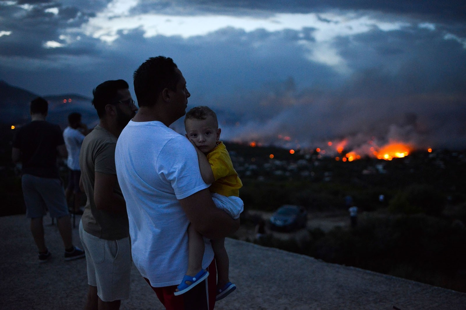 A man holds his son as a wildfire burns in the town of Rafina, near Athens, July 23, 2018.