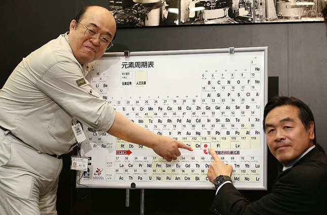 Kosuke Morita (L), who led the team at Riken institute that discovered the superheavy synthetic element, and Hiroshi Hase (R), Minister of Science and Technology, pose with a board displaying the new element 113. (AFP Photo)