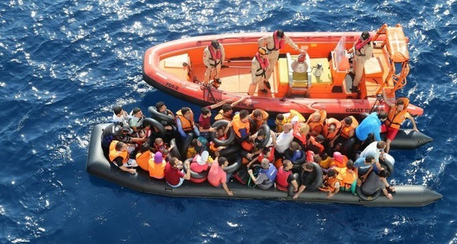 A Turkish Coast Guard boat approaches a raft overcrowded with migrants on the Aegean Sea in this undated photo.