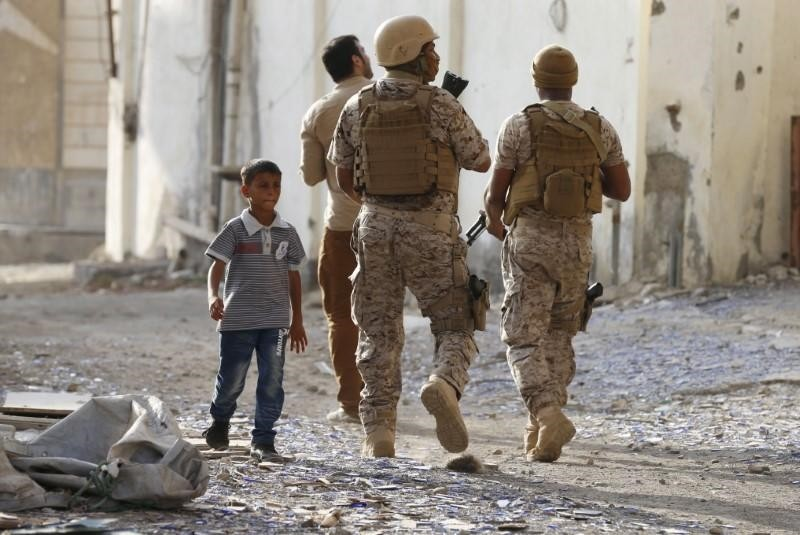 A boy walks past soldiers from the Saudi-led coalition patrolling a street in Yemen's southern port city of Aden September 26, 2015. (Reuters Photo)