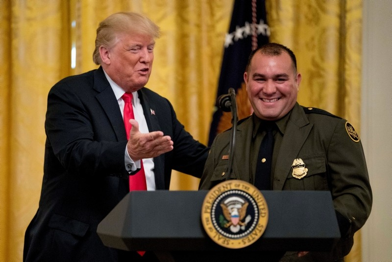 President Donald Trump welcomes Customs and Border Patrol agent Adrian Anzaldua, on stage to speak during the event. (AP Photo)