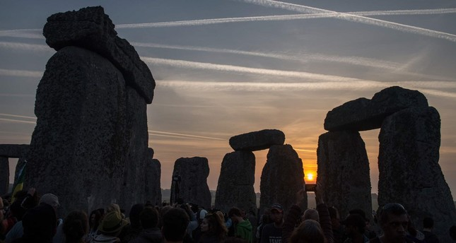 Revellers watch the sunrise as they celebrate the pagan festival of Summer Solstice at Stonehenge in Wiltshire, southern England on June 21, 2017. (AFP Photo)