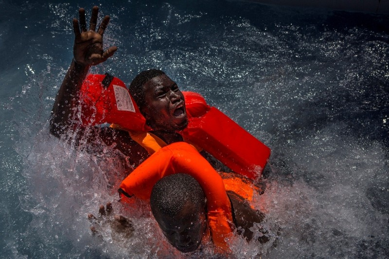 Two men panic and struggle in the water during their rescue. Their rubber boat was in distress and deflating quickly on one side, tipping many migrants in the water. They were quickly reached by rescue swimmers and brought to safety. (EPA Photo)