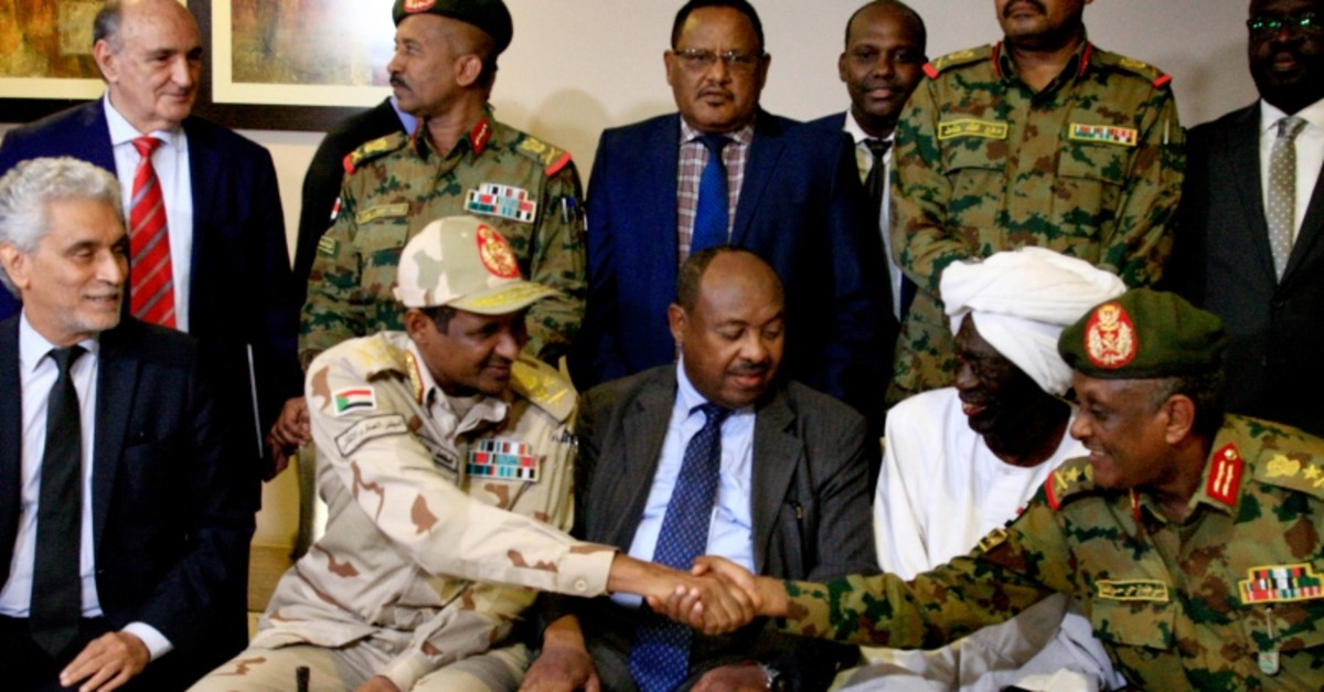 African Union envoy to Sudan Mohammed el-Hassan Labat (L) sits next to Sudan's deputy chief of the ruling military council General Mohamed Hamdan Dagalo as he shakes hands with an army general following a press conference in Khartoum (AFP Photo)