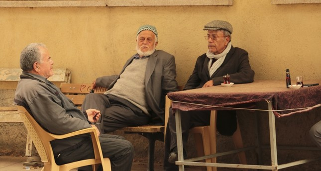 Producer and director Mehmet Taşdiken sitting with villagers.