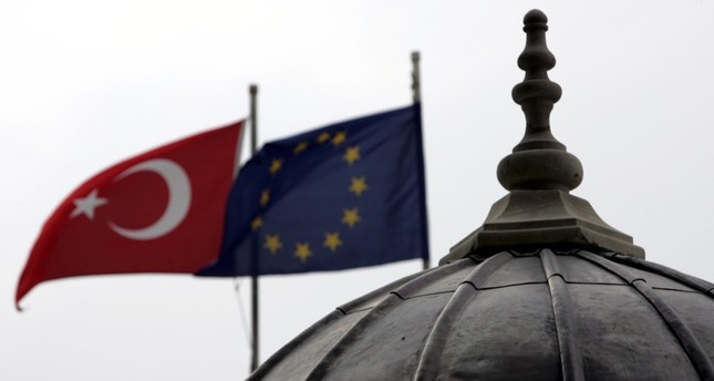 The Turkish and European Union flags waving side by side in Istanbul, where the minarets and domes of mosques and churches dominate the city's silhouette.