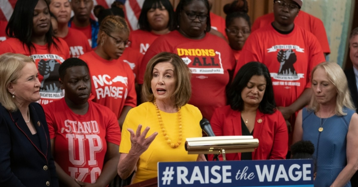 Speaker of the House Nancy Pelosi, D-Calif., joins fellow Democrats and activists as the House approved legislation to raise the federal minimum wage for the first time in a decade, at the Capitol in Washington, July 18, 2019. (AP Photo)